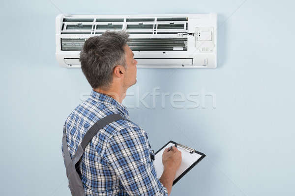 Technician With Clipboard Looking At Air Conditioner Stock photo © AndreyPopov