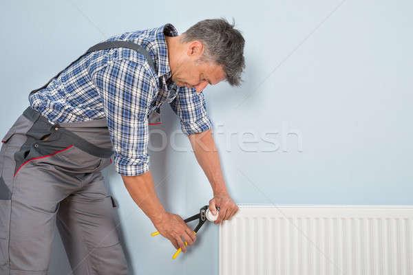 Férfi vízvezetékszerelő megjavít radiátor portré franciakulcs Stock fotó © AndreyPopov