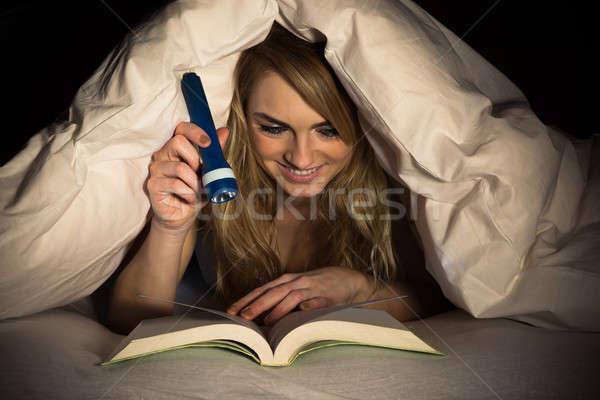 Femme lecture livre lampe de poche jeune femme Photo stock © AndreyPopov