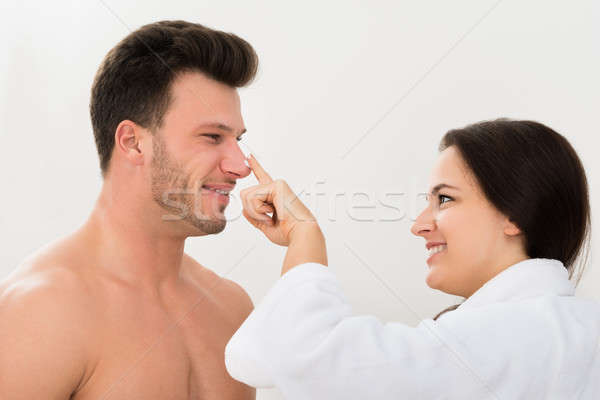 Woman Applying Moisturizer On Man's Nose Stock photo © AndreyPopov