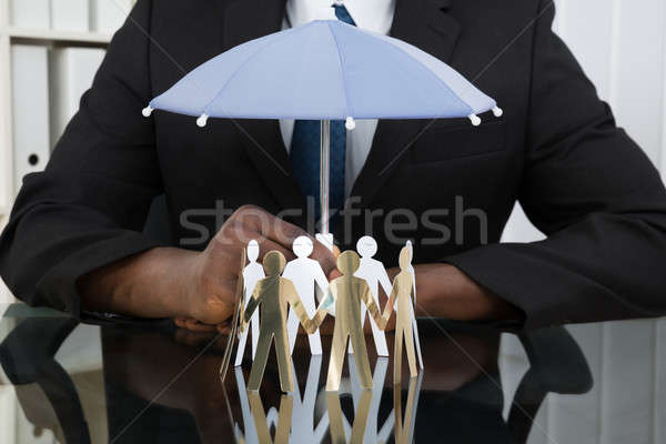 Businessman Holding Umbrella Over Paper Cutout People Stock photo © AndreyPopov