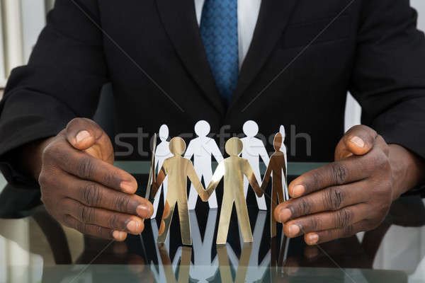 Businessman Protecting Paper Cutout People Stock photo © AndreyPopov