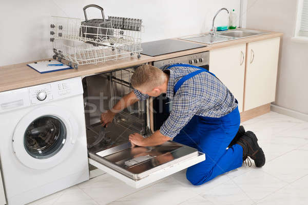 Repairman Fixing Dishwasher Stock photo © AndreyPopov
