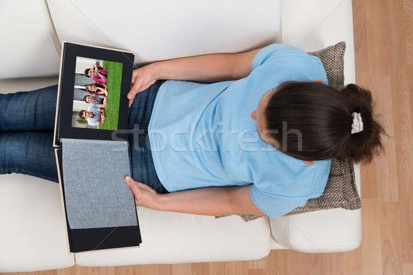 Nő néz család fényképalbum ül kanapé Stock fotó © AndreyPopov