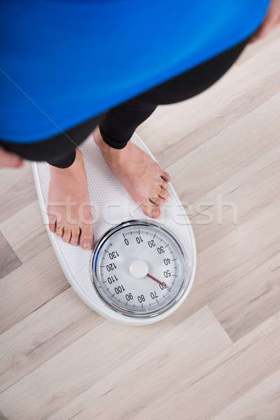 Woman Measuring Weight On Weighing Scale Stock photo © AndreyPopov