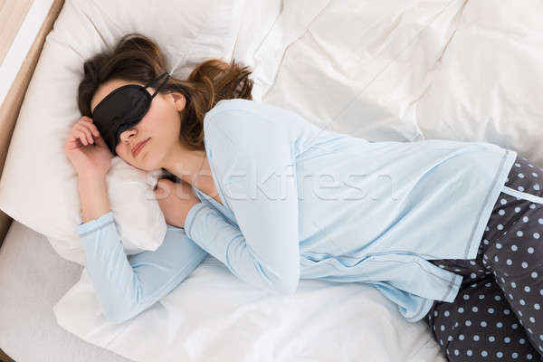 Woman Wearing Eyemask While Sleeping On Bed Stock photo © AndreyPopov