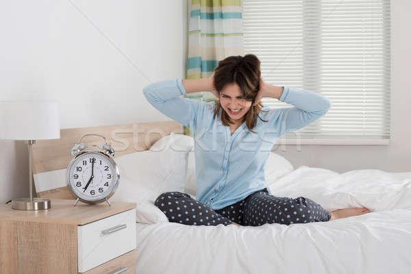 Kimerült nő ébresztőóra fiatal nő hálószoba óra Stock fotó © AndreyPopov