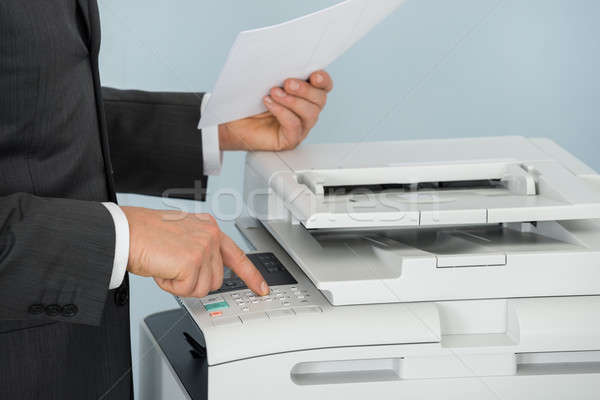 Close-up Of Businessman Pressing Printer's Button In Office Stock photo © AndreyPopov