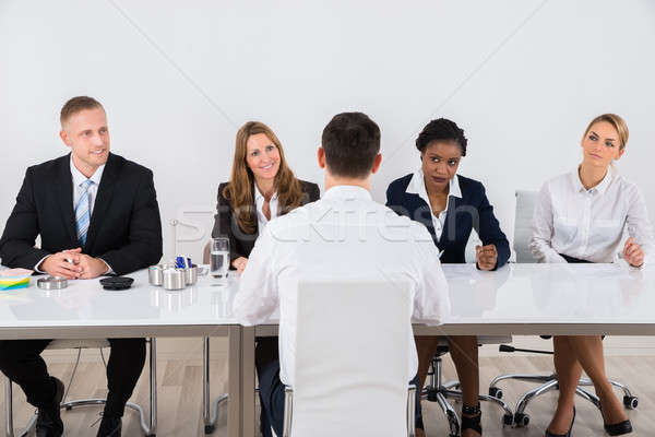 Businesspeople Interviewing Man Stock photo © AndreyPopov