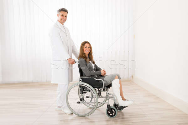 Doctor Assisting Woman On Wheelchair Stock photo © AndreyPopov