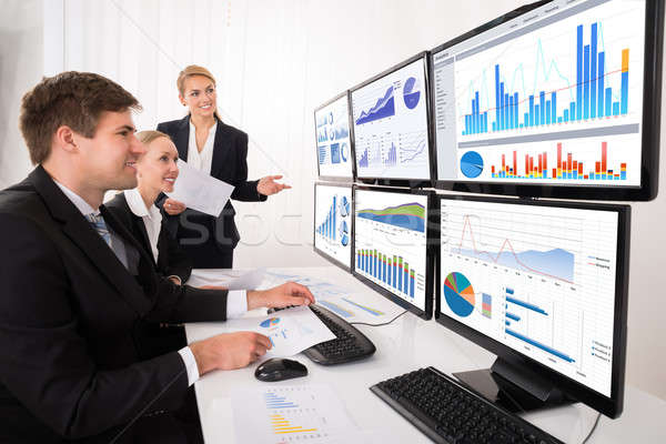 Businesspeople Looking At Financial Graphs On Multiple Computer Stock photo © AndreyPopov