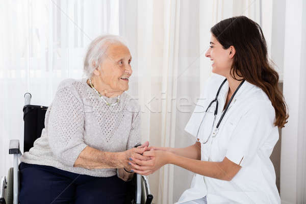 Female Doctor Consoling Handicapped Senior Patient Stock photo © AndreyPopov