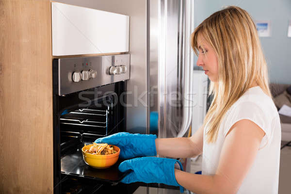 Happy Woman Preparing Food In Oven Stock photo © AndreyPopov
