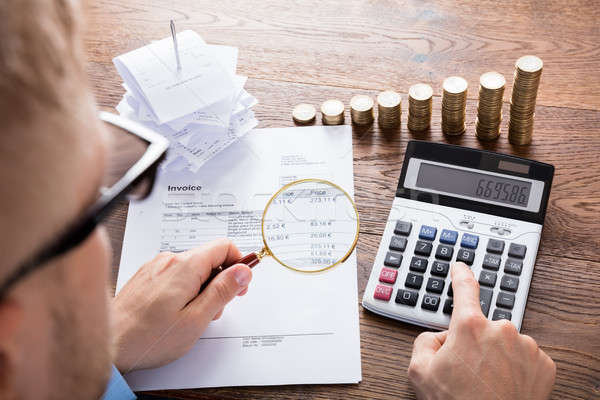 Person Calculating Invoice On Desk Stock photo © AndreyPopov