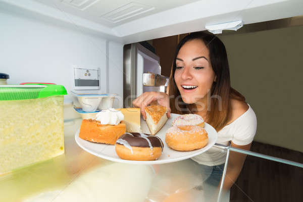 Woman Taking The Slice Of Cake From Refrigerator Stock photo © AndreyPopov