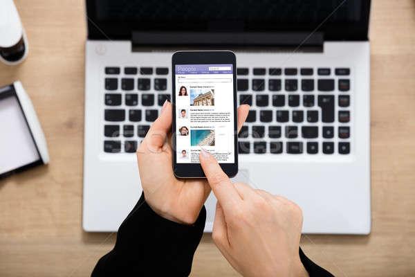 Businesswoman Using Social Network On Mobilephone Stock photo © AndreyPopov