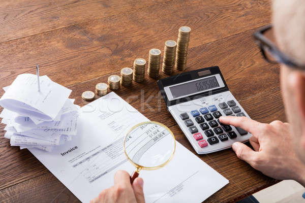 Person Calculating Invoice On Desk Stock photo © AndreyPopov