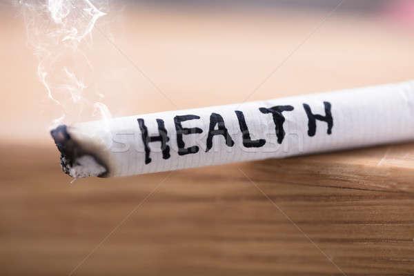 Salute rischio brucia sigaretta primo piano parola Foto d'archivio © AndreyPopov