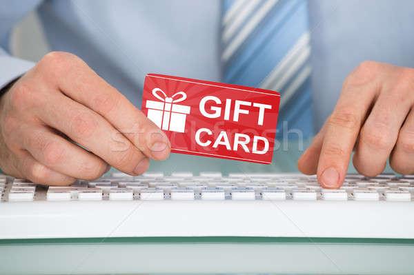 Geschäftsmann halten rot Geschenkkarte Hand Tastatur Stock foto © AndreyPopov