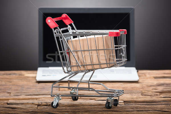 Cardboard Box In Shopping Cart With Laptop On Wooden Table Stock photo © AndreyPopov