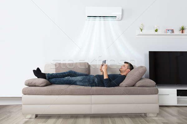 男 ソファ 空調装置 タブレット 若い男 ホーム ストックフォト © AndreyPopov