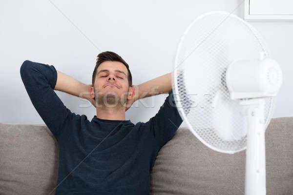 Homem sessão sofá resfriamento ventilador Foto stock © AndreyPopov