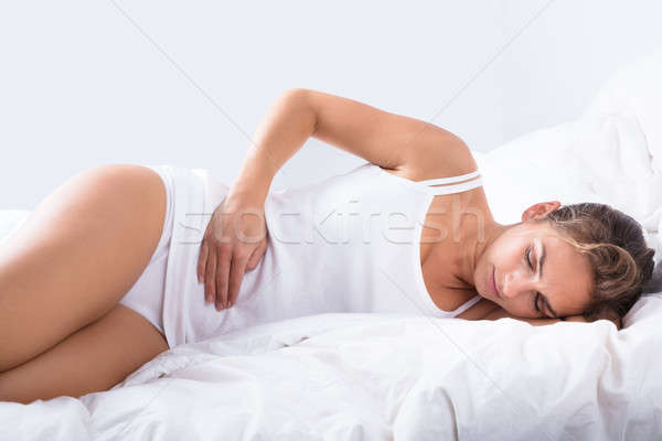Nő alszik ágy gyomorfájás kilátás otthon Stock fotó © AndreyPopov