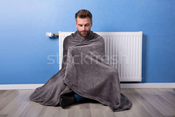 Man Sitting In Front Of Heater At Home Stock photo © AndreyPopov