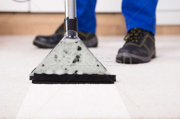 Person Using Vacuum Cleaner For Cleaning Carpet Stock photo © AndreyPopov