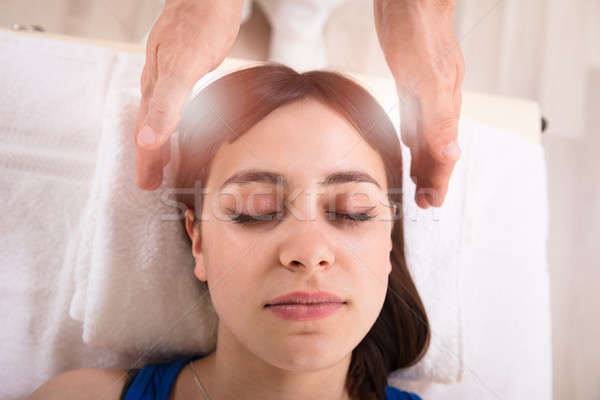 Woman Receiving Reiki Treatment By Therapist Stock photo © AndreyPopov