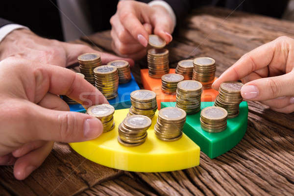Businesspeople Stacking Coins On Pie Chart Stock photo © AndreyPopov