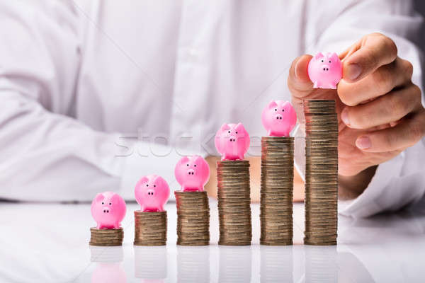 Person Placing Piggybank On Increasing Stacked Coins Stock photo © AndreyPopov