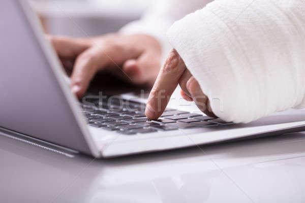 Uomo fasciatura mano utilizzando il computer portatile primo piano lavoro Foto d'archivio © AndreyPopov