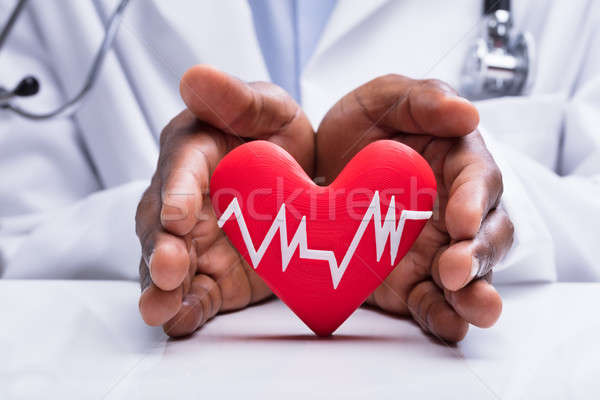 Doctor Protecting Heart With Heartbeat Pulse Icon Stock photo © AndreyPopov