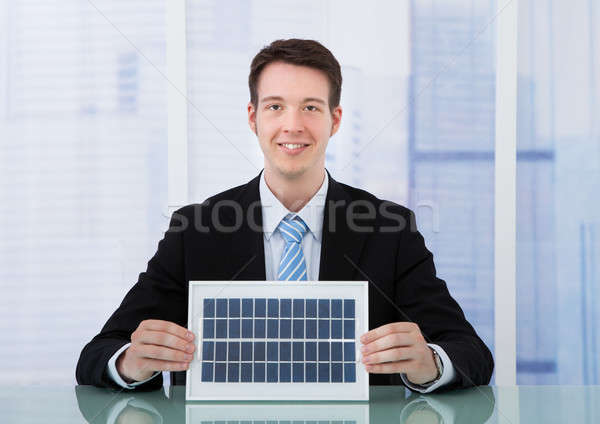 Confident Businessman Holding Solar Panel At Desk Stock photo © AndreyPopov