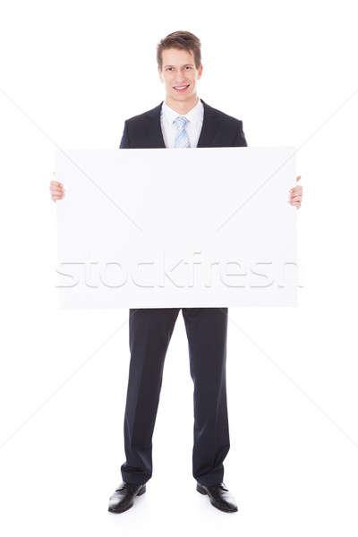 üzletember tart plakát portré fiatal fehér Stock fotó © AndreyPopov