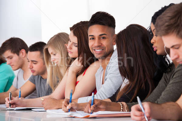 Confident Student Sitting With Classmates Writing At Desk Stock photo © AndreyPopov