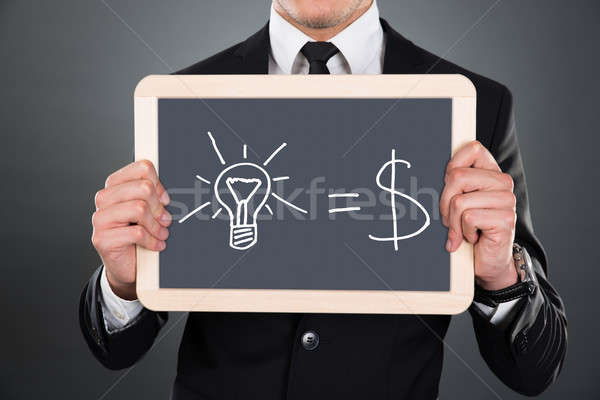 Businessman Holding Slate With Idea Equation Stock photo © AndreyPopov
