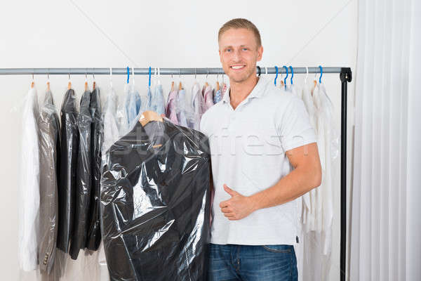 Young Man With Coat In Dry Cleaning Store Stock photo © AndreyPopov