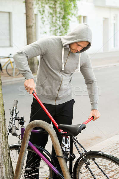 Thief Trying To Break The Bicycle Lock Stock photo © AndreyPopov