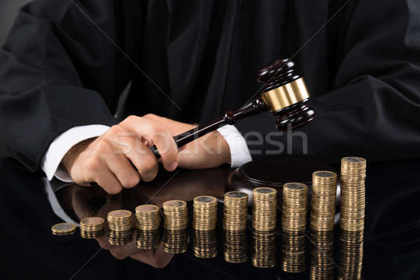 Judge Hitting Gavel In Front Of Coins Stock photo © AndreyPopov