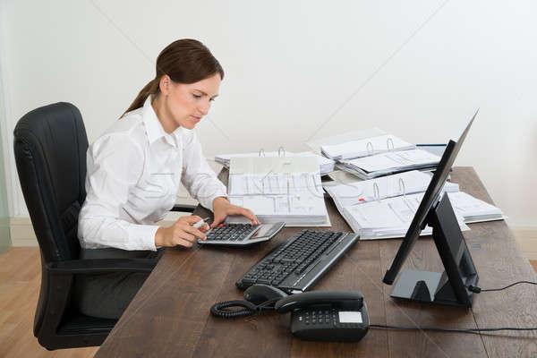Contador cálculo secretária jovem feminino calculadora Foto stock © AndreyPopov