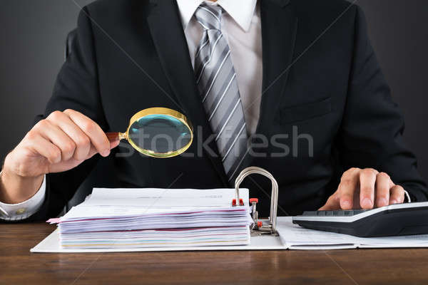 Businessman Inspecting Invoice With Magnifying Glass Stock photo © AndreyPopov