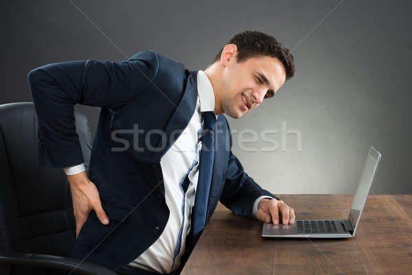 Businessman Suffering From Back Pain While Working On Laptop Stock photo © AndreyPopov
