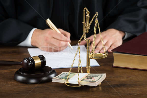 Judge Writing On Document With Banknotes In Weight Scale Stock photo © AndreyPopov
