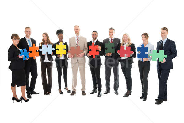 Portrait Of Happy Business Team Holding Jigsaw Pieces Stock photo © AndreyPopov