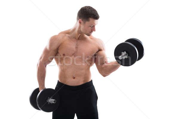 Determinado muscular homem halteres branco Foto stock © AndreyPopov