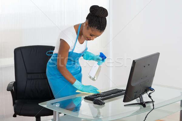 Mulher limpeza secretária trapo sorridente jovem Foto stock © AndreyPopov