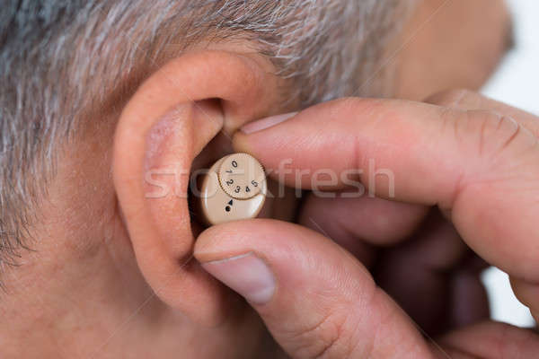 Closeup Of Businessman Inserting Hearing Aid In Ear Stock photo © AndreyPopov