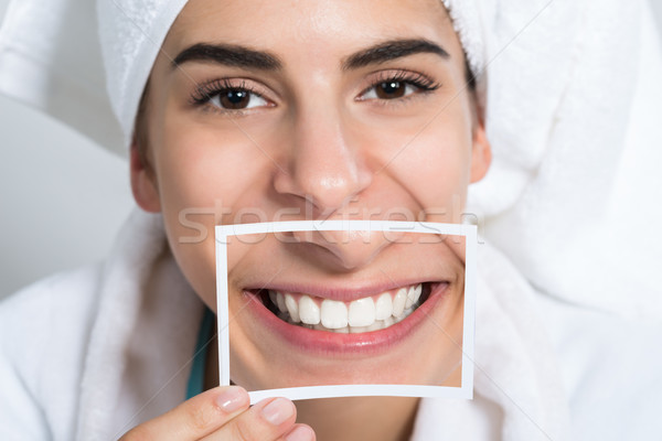 Woman Holding Photo Of Toothy Smile Stock photo © AndreyPopov